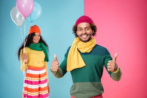 風船が立っている女の子を笑顔しながら親指を表示して幸せなアフリカの若い男