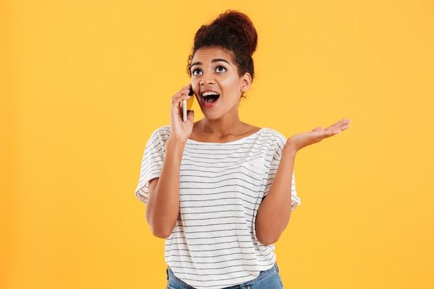 Счастливая африканская молодая женщина с открытым ртом говоря на изолированном телефоне