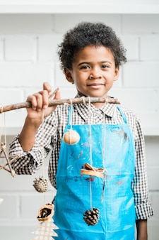 スレッドに掛かっている手作りのクリスマス装飾が付いている棒を保持している青いエプロンで幸せなアフリカの若者