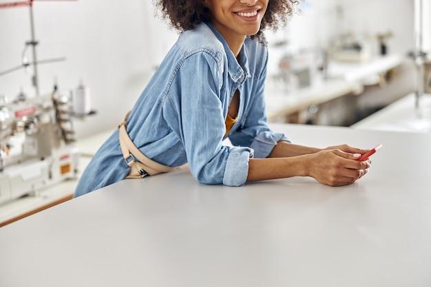 幸せなアフリカ系アメリカ人の従業員は、ワークショップのクローズアップでカッティングテーブルに寄りかかって携帯電話を保持します
