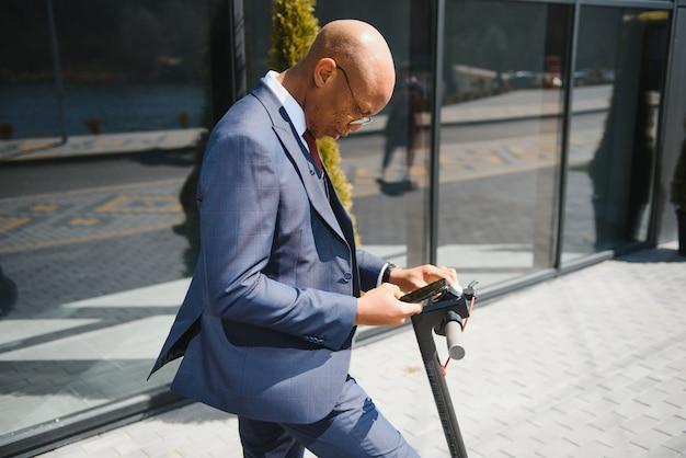 大都市でのe-スクーターに乗っている間に彼の電話をチェックしている幸せなアフロ30代の男性
