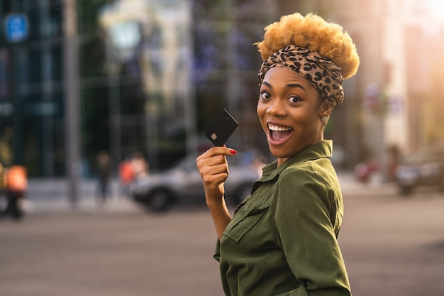 Happy afro american beautiful woman walking on the street while holding debit card