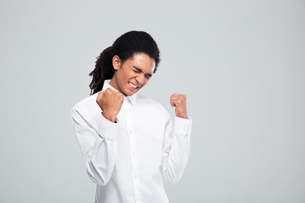Счастливый афро-американский бизнесмен празднует свой успех на сером фоне
