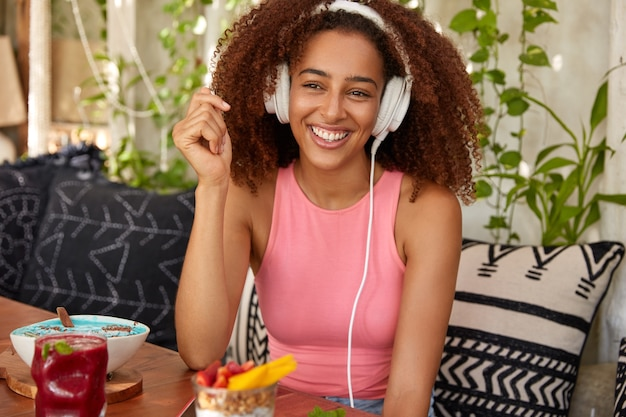 Happy afro american female meloman listens music with high volume in headphones