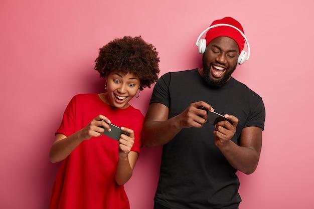 행복한 아프리카 계 미국인 여자 친구와 남자 친구가 휴대폰으로 게임을하고 온라인 경쟁에서 경쟁하며 함께 즐거운 시간을 보내십시오.