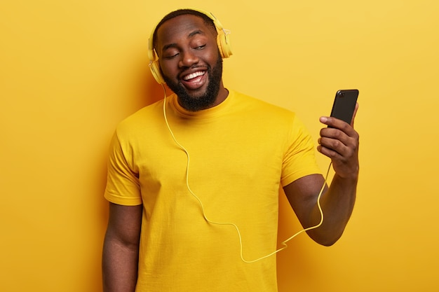 Happy afro american man enjoys song to sing along, holds modern cell phone connected to headphones