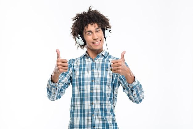 ヘッドフォンで音楽を聴き、白い壁に隔離された親指を見せて幸せなアフリカ系アメリカ人の男