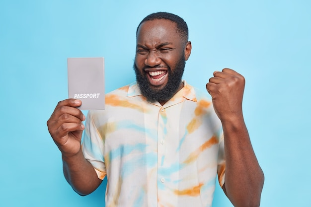 Happy afro american man rejoices getting new passport poses with official document wears casual shirt has upbeat mood allowed to travel internationally isolated over blue wall