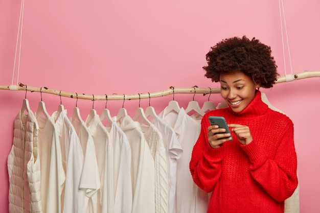 Happy afro american manager of online shop, consults clients, types comment, sells new collection in white color, wears knitted red sweater, stands near rack, isolated over pink wall.
