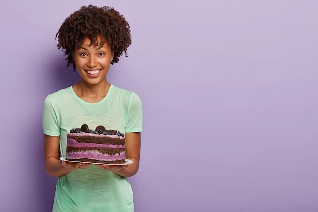 Счастливая афроамериканка держит вкусный праздничный торт с черникой, угощает гостей вкусным сладким десертом