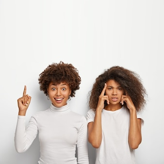 Una donna afroamericana felice indica sopra l'indice, il suo intenso amico tocca le tempie, cerca di ricordare informazioni importanti