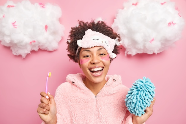 Happy afro american woman smiles broadly enjoys good morning brushes teeth and undergoes beauty applies pads procedures holds toothbrush and bath sponge wears sleepmask on forehead