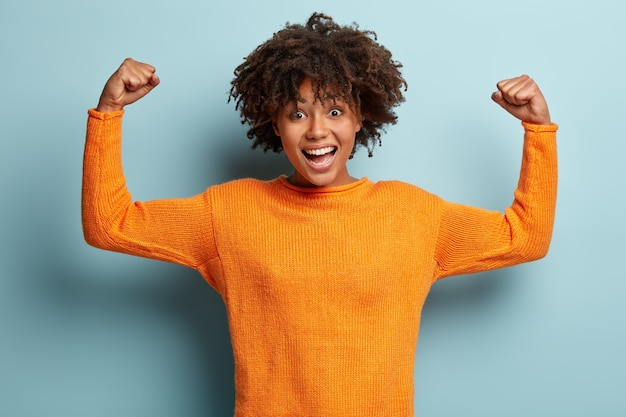 Happy afro american woman with curly hair, raises hands and shows muscles, demonstrates her strength, wears orange jumper Free Photo
