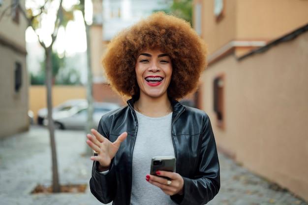路上で彼女のスマートフォンと幸せなアフリカ系アメリカ人の女性