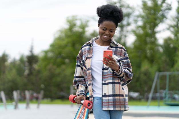 행복한 아프리카 소녀 메시지는 야외에서 롱보드와 휴대전화를 들고 스마트폰 캐주얼 여성을 잡고 있습니다.