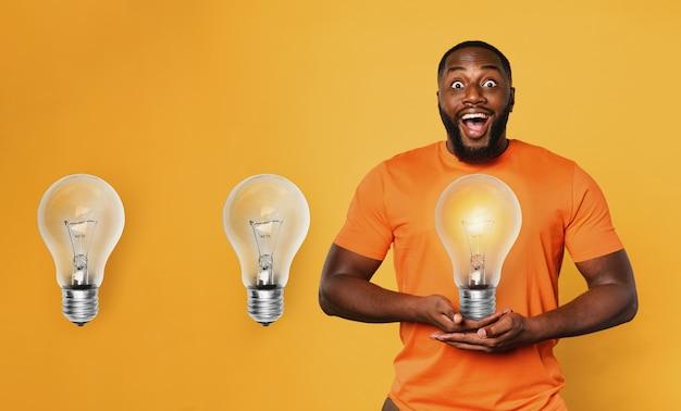 Счастливый афро-мужчина держит лампочку руками. понятие об идее и творчестве. оранжевый фон