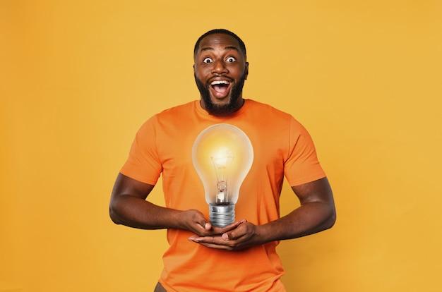 Счастливый афро-мужчина держит лампочку руками.