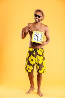Счастливый афро-мужчина в купальниках, указывая пальцем на настенные часы, изолированные на оранжевой стене