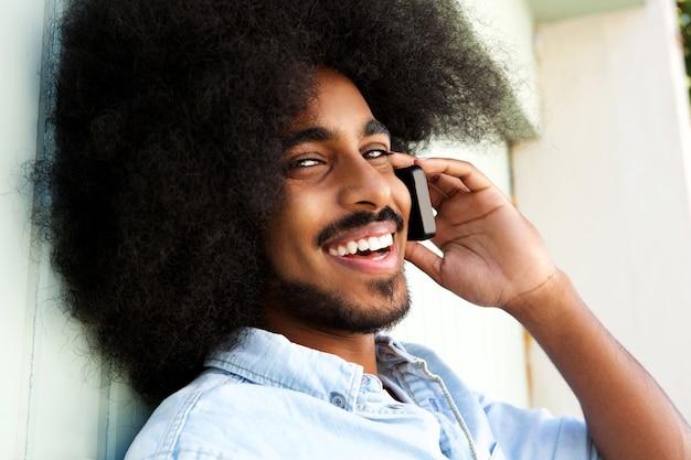 携帯電話で話して笑っている幸せなアフロ男