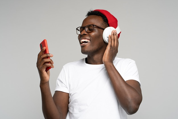 Happy afro man wear wireless headphones enjoying listening to music, dancing, using smartphone