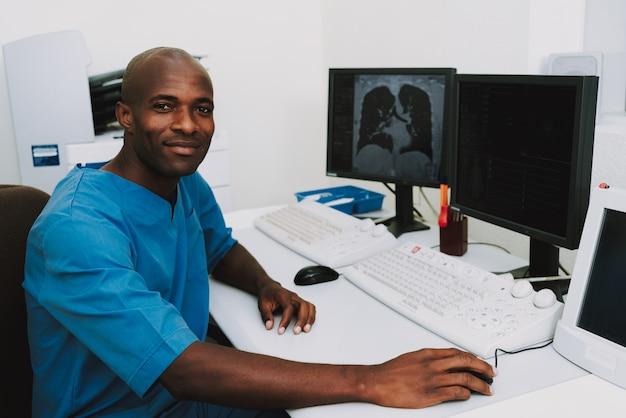 Happy afro radiology professional анализирующее сканирование.