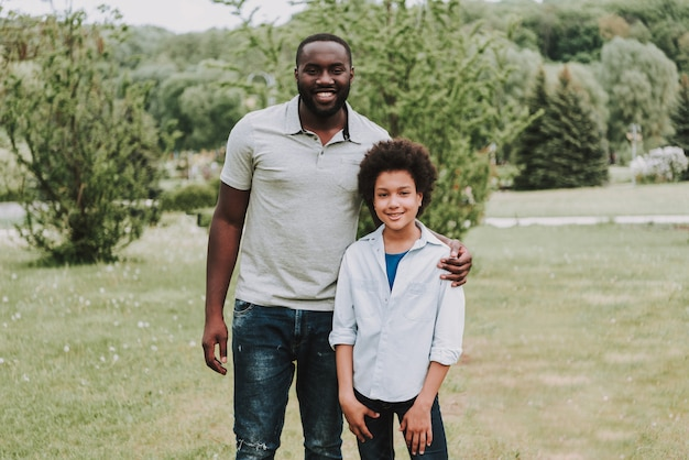 Happy afro son and father relaxing in nature