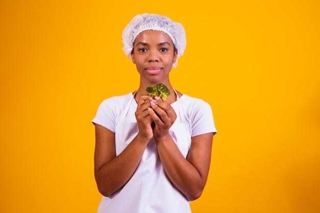 Счастливая афро женщина ест брокколи. женщина с брокколи на желтом фоне. концепция здорового питания