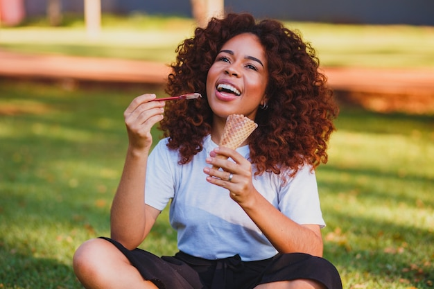 Happy afro woman eating ice cream in the park