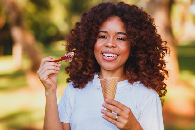 Happy afro woman eating ice cream in the park.
