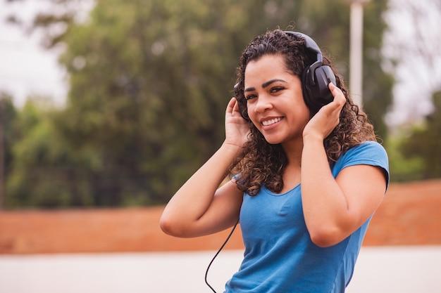 彼女のヘッドフォンで音楽を聴いて幸せなアフロ女性。