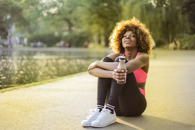 Happy afro woman relaxing after jogging