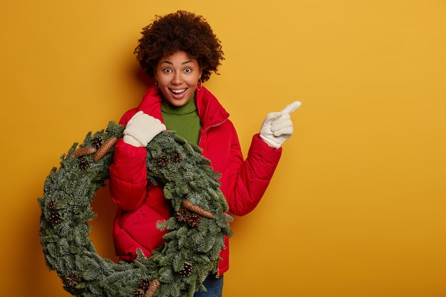 Happy afro woman shows way to her house, wears red coat, white gloves, carries christmas wreath, points at blank space, stands against yellow background