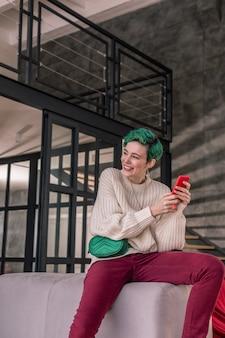 メッセージの後に幸せです。素敵な彼氏からメッセージをもらって幸せな気持ちになる緑髪の女性