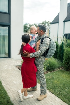 Happy after reunion. family feeling truly happy after reunion while husband returning from military service