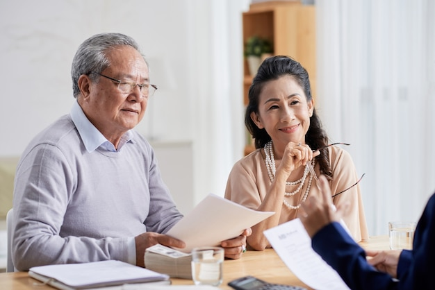 Happy aged couple meeting with real estate manager filling document and making payment for new house