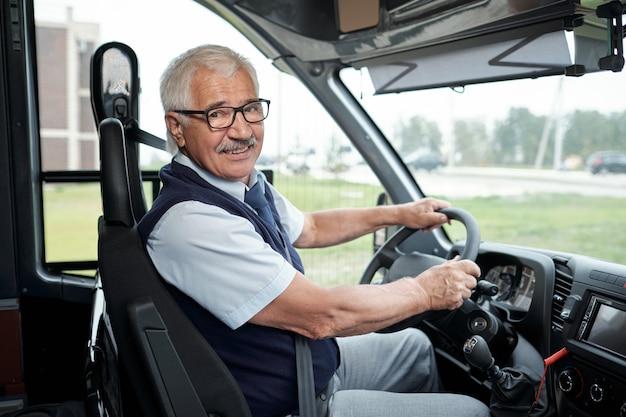 Счастливый пожилой водитель междугороднего автобуса, держащийся за руль