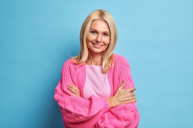 幸せな年配のおばあちゃんは優しい笑顔で見え、カジュアルなニットセーターを着てリラックスしたポーズで腕を組んで立っています。