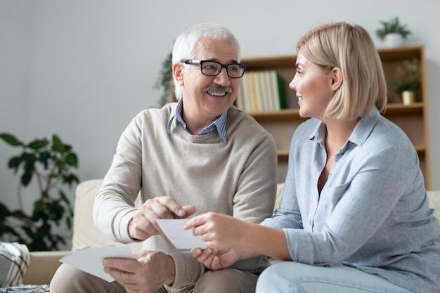 Счастливый пожилой мужчина, указывая на фото в руке дочери, одновременно отдыхая дома на досуге и обсуждая фотографии