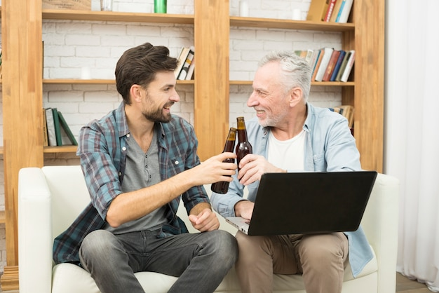 Happy aged man and young guy clanging bottles and using laptop on sofa