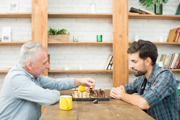 Happy aged man and young guy playing chess at table in room