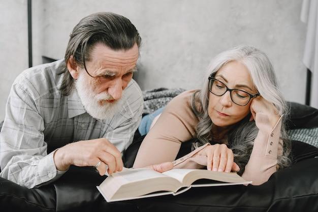 家で一緒にリラックスして幸せな老夫婦。ベッドで本を読んでいる年配のカップル。