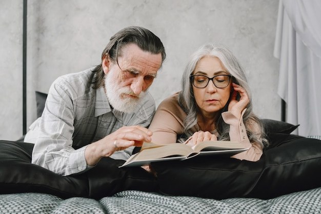 Happy aged married couple relaxing together at home. senior couple reading book on bed.