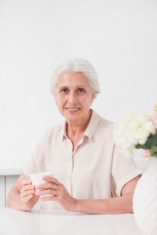 Happy aged woman holding white cup of coffee