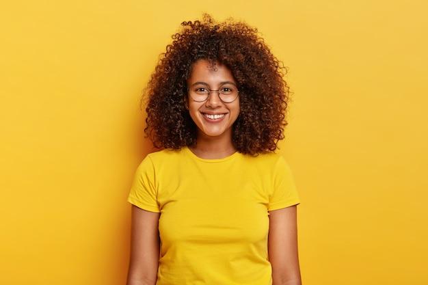 곱슬 검은 머리를 가진 행복하고 매혹적인 젊은 여성은 흥미 진진한 이벤트를 기대하고 즐겁게 웃으며 큰 둥근 spetacles와 노란색 티셔츠를 입습니다.
