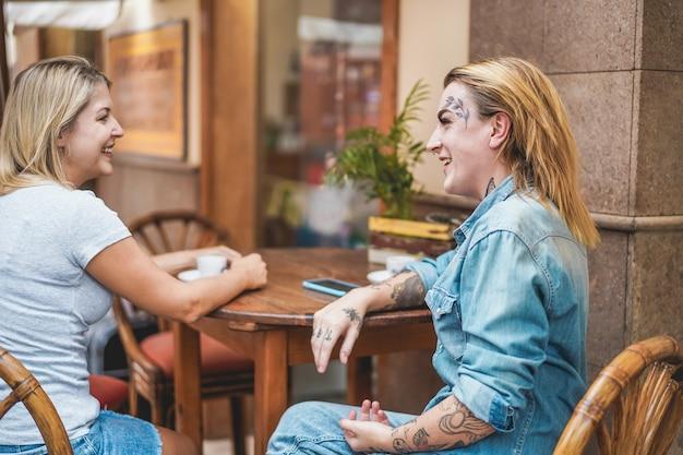 Счастливая альтернативная женщина разговаривает со своим другом в кафе-баре