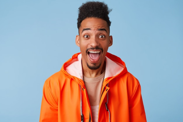 Happy amazed attractive african american dark skinned boy wears in orange rain coat, with wide open mouth, smiles broadly stands
