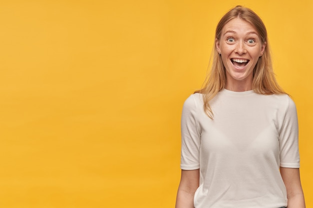 Happy amazed blonde young woman with freckles in white tshirt looks surprised and looking at camera over yellow wall