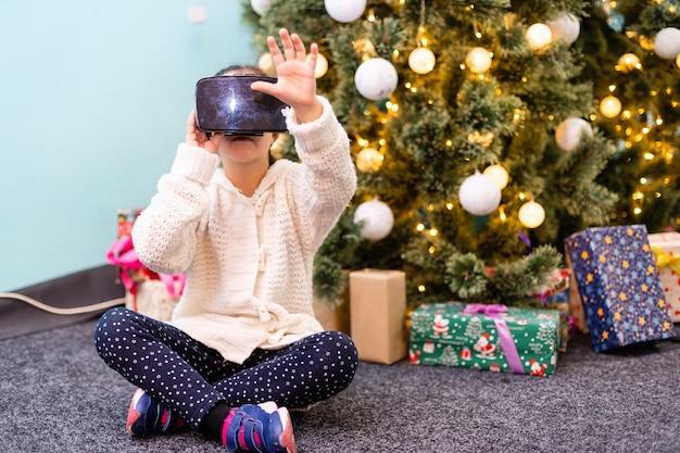 가상 현실 고글을 쓰고 영화를 보거나 비디오 게임을 하는 행복한 어린 소녀는 크리스마스 배경에서 격리되어 있습니다. vr 안경을 보고 자신의 손으로 몸짓을 하는 쾌활한 놀란 아이