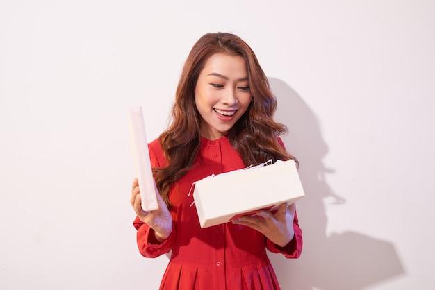 赤いドレスを着た巻き毛の幸せな驚きのレトロなスタイルの女性が白い壁にプレゼントを開きました
