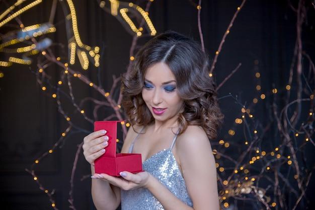 Счастливая изумленная стильная женщина с вьющимися волосами в блестящем серебряном платье открыла подарок на темном фоне